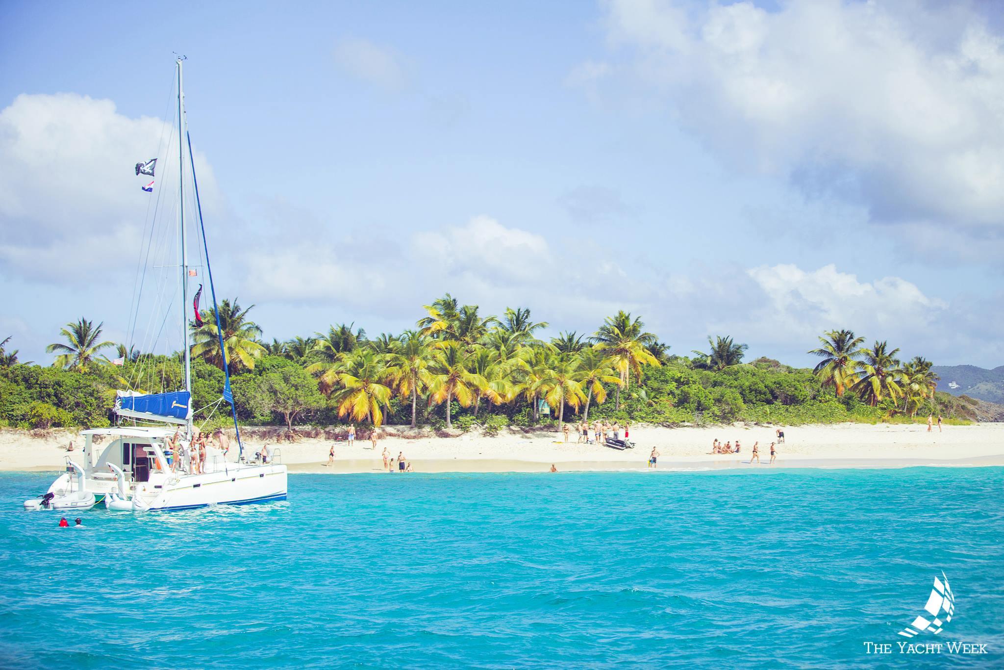 Catamaran in front on a white sand beach bvi